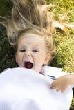 Λίγο χαριτωμένο ξανθό κορίτσι στο πάρκο που βάζει στο πράσινο χαμόγελο χλόης, που κρατά το άσπρο θερινό καπέλο συναισθηματικό, άν Στοκ Φωτογραφία