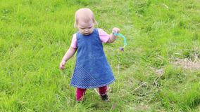 Λίγο χαριτωμένο ξανθό κορίτσι στο φόρεμα πηγαίνει στην πράσινη χλόη απόθεμα βίντεο