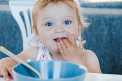 Λίγο χαριτωμένο ξανθό μπλε-eyed κορίτσι που τρώει τα ζυμαρικά με τα χέρια στοκ εικόνα
