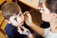 Λίγο χαριτωμένο παιδί που κάνει facepaint στη γιορτή γενεθλίων, zombie αποκάλυψης, αποκριές που προετοιμάζει την έννοια Στοκ φωτογραφία με δικαίωμα ελεύθερης χρήσης