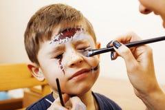 Λίγο χαριτωμένο παιδί που κάνει facepaint στη γιορτή γενεθλίων, zombie αποκάλυψης, αποκριές που προετοιμάζει την έννοια Στοκ Εικόνες