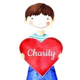 Λίγο χαριτωμένο χαμογελώντας αγόρι που κρατά μια μεγάλη κόκκινη καρδιά στα χέρια του φιλανθρωπία Στοκ Φωτογραφία