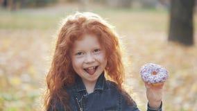 Λίγο χαριτωμένο redhead κορίτσι που στέκεται σε ένα πάρκο φθινοπώρου με doughnut στο χέρι της και που εξετάζει τη κάμερα Πορτρέτο απόθεμα βίντεο