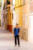 Λίγο όμορφο αγόρι που περπατά στην ευρωπαϊκή οδό πόλεων με το σακίδιο πλάτης του Στοκ Φωτογραφίες