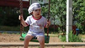 Λίγο όμορφο αγόρι στην ταλάντευση γυαλιών στην παιδική χαρά φιλμ μικρού μήκους