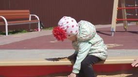 Λίγο όμορφο καυκάσιο κορίτσι 3 χρονών παίζει σε ένα Sandbox με τα παιχνίδια και τα Sandbox, παιδική χαρά απόθεμα βίντεο