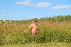 Λίγο όμορφο κορίτσι πηγαίνει μεταξύ της χλόης στο πράσινο λιβάδι Στοκ φωτογραφία με δικαίωμα ελεύθερης χρήσης