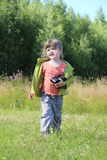Λίγο όμορφο κορίτσι πηγαίνει με τη κάμερα μεταξύ της πράσινης χλόης Στοκ Εικόνα