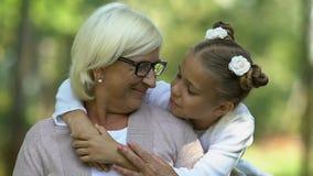 Λίγο όμορφο κορίτσι που αγκαλιάζει και που φιλά την παλαιά γιαγιά της, καλή οικογένεια φιλμ μικρού μήκους