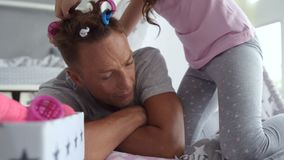 Λίγο όμορφο κορίτσι που βάζει τα ρόλερ τρίχας στην τρίχα πατέρων της φιλμ μικρού μήκους
