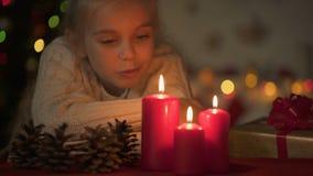 Λίγο όμορφο κορίτσι που εξετάζει το κάψιμο των κεριών, που περιμένουν τον εορτασμό Χριστουγέννων απόθεμα βίντεο