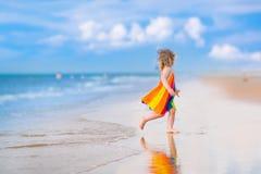Λίγο όμορφο κορίτσι που τρέχει σε μια παραλία Στοκ Εικόνες