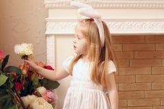 Λίγο όμορφο κορίτσι στα άσπρα αυτιά φορεμάτων και λαγουδάκι Στοκ Φωτογραφίες