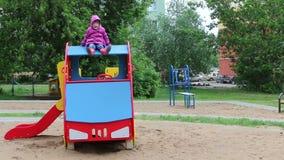 Λίγο όμορφο κορίτσι στα gumboots κάθεται στο ξύλινο αυτοκίνητο στην παιδική χαρά απόθεμα βίντεο