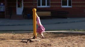 Λίγο όμορφο κορίτσι στη ρόδινη ταλάντευση στην παιδική χαρά απόθεμα βίντεο