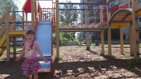 Λίγο όμορφο κορίτσι στους ρόδινους ρόλους γλιστρά κάτω στην παιδική χαρά απόθεμα βίντεο