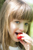 Λίγο όμορφο κορίτσι τρώει τις juicy φρέσκες φράουλες στοκ φωτογραφίες