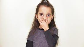 Λίγο όμορφο λυπημένο κορίτσι παρουσιάζει οι συγκίνησης δυσαρέσκεια, θυμός, εξετάζει κάμερα, πορτρέτο, άσπρος υπόβαθρο 50 fps φιλμ μικρού μήκους