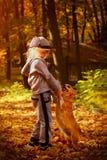 Λίγο όμορφο παιχνίδι κοριτσιών με ένα σκυλί στο πάρκο φθινοπώρου Στοκ Φωτογραφία