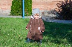 Λίγο όμορφο παλτό, καπέλο και τζιν μωρών κοριτσιών που παίζουν στο πάρκο που περπατά στην πράσινη χλόη που κάνει το πρώτα χαμόγελ Στοκ φωτογραφίες με δικαίωμα ελεύθερης χρήσης