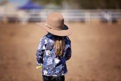 Λίγο Cowgirl που στέκεται στη σκόνη που προσέχει ένα ροντέο Στοκ Εικόνες