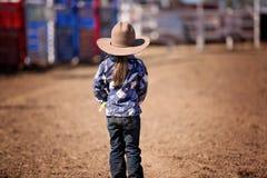 Λίγο Cowgirl στέκεται στη σκόνη προσέχοντας ένα ροντέο χώρας Στοκ Εικόνα