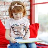 Λίγο preschooler κάθεται στη στρωματοειδή φλέβα και το σχεδιασμό παραθύρων στοκ φωτογραφίες