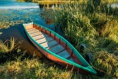 Λίμνη ή ποταμός και παλαιό ξύλινο μπλε αλιευτικό σκάφος κωπηλασίας σε όμορφο Στοκ Φωτογραφία