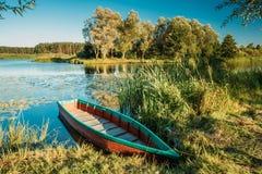 Λίμνη ή ποταμός και παλαιό ξύλινο μπλε αλιευτικό σκάφος κωπηλασίας σε όμορφο Στοκ Εικόνα
