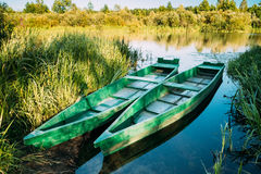 Λίμνη ή ποταμός και δύο παλαιά ξύλινα μπλε αλιευτικά σκάφη κωπηλασίας στην όμορφη θερινή ηλιόλουστη ημέρα Στοκ φωτογραφία με δικαίωμα ελεύθερης χρήσης