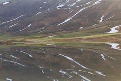 Λίμνη βουνών με το λειώνοντας χιόνι Στοκ Φωτογραφία