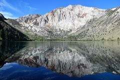 Λίμνη βουνών που αντανακλάται ενάντια στο φωτεινό μπλε ουρανό στοκ φωτογραφίες