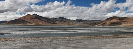 Λίμνη βουνών, τοπίο: στο πρώτο πλάνο τα μπλε νερά της λίμνης, πίσω από το βουνό αλυσοδένουν, πανόραμα φωτογραφιών, τα Ιμαλάια Στοκ Εικόνες