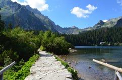 Λίμνη βουνών Pleso Popradske στην υψηλή σειρά βουνών Tatras στη Σλοβακία - μια όμορφη ηλιόλουστη θερινή ημέρα σε μια δημοφιλή πεζ Στοκ Εικόνες