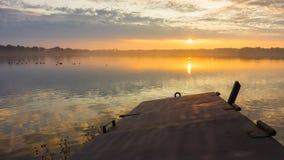 Λίμνη κάτω από το χρυσό ουρανό από το ηλιοβασίλεμα απόθεμα βίντεο