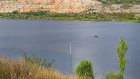 Λίμνη και ψαράδες βουνών σε μια βάρκα στοκ φωτογραφίες