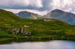Λίμνη μεταξύ των χλοωδών κλίσεων με τους λίθους Στοκ εικόνες με δικαίωμα ελεύθερης χρήσης