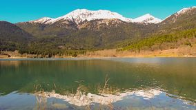 Λίμνη Doxa στην Πελοπόννησο Ελλάδα ενάντια στο χιονώδες βουνό απόθεμα βίντεο