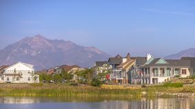 Λίμνη Oquirrh με τα σπίτια ενάντια στο βουνό και τον ουρανό στοκ εικόνα