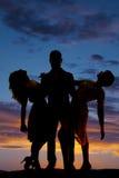 Λαβή ανδρών σκιαγραφιών δύο γυναίκες που κλίνουν το πίσω ηλιοβασίλεμα Στοκ Εικόνα