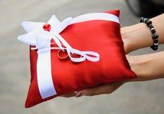 Λαβή γυναικών ένα κόκκινο μαξιλάρι με τα χρυσά γαμήλια δαχτυλίδια Στοκ Εικόνες