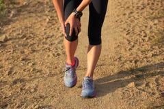Λαβή δρομέων τραυματισμένο το αθλητισμός γόνατό της στο βρώμικο δρόμο Στοκ φωτογραφία με δικαίωμα ελεύθερης χρήσης