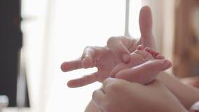 Λαβή μητέρων τα πόδια μωρών της απόθεμα βίντεο