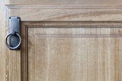 Λαβή χαλκού με το δαχτυλίδι στη δρύινη πόρτα με τις επιτροπές στοκ εικόνα
