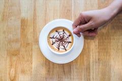 Λαβή χεριών ένα φλιτζάνι του καφέ στο ξύλινο υπόβαθρο Στοκ Εικόνες