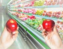 Λαβή δύο χεριών και επιλογή του μήλου Στοκ Φωτογραφία