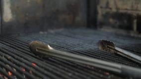 Λαβίδες μετάλλων Φλόγες και κόκκινη αργεντινή σχάρα χοβόλεων Πυρκαγιά και προετοιμασία σχαρών για τη σχάρα στο εστιατόριο Steakho φιλμ μικρού μήκους