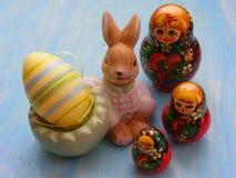 Λαγοί Πάσχας με το χρωματισμένο matreshka κουκλών αυγών και matrioshka κουκλών στο μπλε ξύλινο υπόβαθρο Στοκ φωτογραφία με δικαίωμα ελεύθερης χρήσης