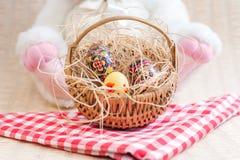Λαγουδάκι τρωγόντων που κρατά ένα καλάθι αυγών Πάσχας Στοκ εικόνες με δικαίωμα ελεύθερης χρήσης