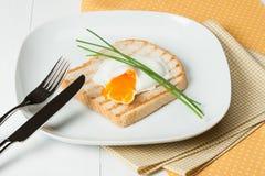 Λαθραίο αυγό στη φρυγανιά με τα φρέσκα κρεμμύδια λευκό πιάτων Στοκ Εικόνες